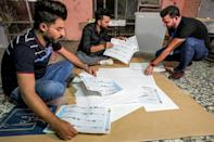Iraqi election officials on Sunday conducted a manual count of votes as part of the verification process for the electronic count, at a polling station in Baghdad (AFP/Ahmad Al-Rubaye)