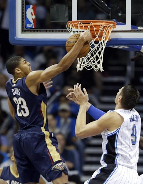 New Orleans Pelicans' Anthony Davis (23) grabs an offensive rebound away from Orlando Magic's Nikola Vucevic (9), of Montenegro, during the first half of an NBA basketball game in Orlando, Fla., Friday, Nov. 1, 2013. (AP Photo/John Raoux)