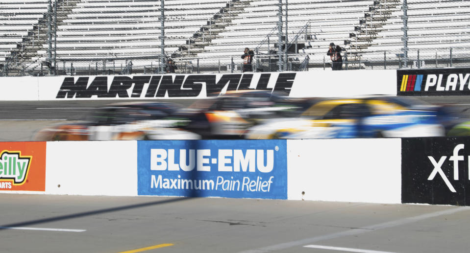 A tight group of drivers speed around Turn 3 during a NASCAR Xfinity Series auto race at Martinsville Speedway in Martinsville, Va., Saturday, Oct. 31, 2020. (AP Photo/Lee Luther Jr.)