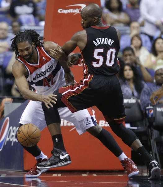 Washington Wizards forward Nene, left, of Brazil, and Miami Heat forward Joel Anthony scramble for the ball during the first half of an NBA basketball game Wednesday, April 10, 2013, in Washington. (AP Photo/Evan Vucci)