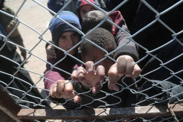 Children look through a chain link fence at the al-Hol displacement camp in Hasaka governorate, Syria, March 8, 2019. (Issam Abdallah/Reuters - image credit)