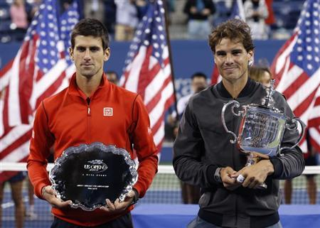 Rafael Nadal of Spain poses with his trophy after defeating Novak Djokovic of Serbia (L, with runner up trophy) in their men's final match at the U.S. Open tennis championships in New York, September 9, 2013. REUTERS/Mike Segar