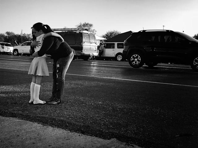 Meredith Cooper, from nearby San Antonio, comforts her 8-year-old daughter, Heather, across the street from the First Baptist Church in Sutherland Springs, Texas, the site of Sunday's mass shooting. (Photo: Holly Bailey/Yahoo News)