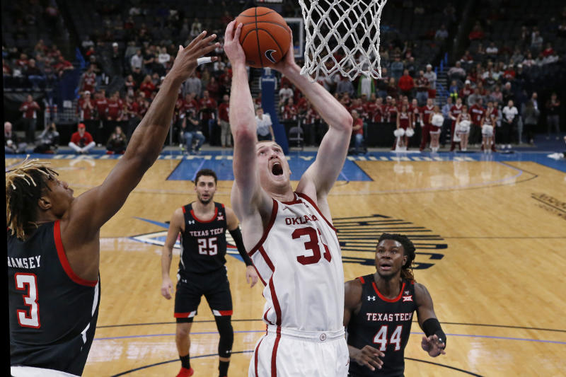 Oklahoma forward Brady Manek (35) shoots between Texas Tech guard Jahmi'us Ramsey (3) and guard Chris Clarke (44) in the second half of an NCAA college basketball game Tuesday, Feb. 25, 2020, in Oklahoma City. (AP Photo/Sue Ogrocki)