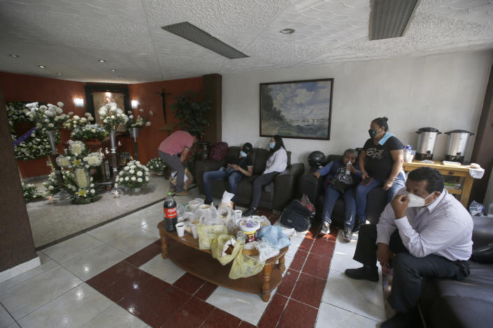 Friends and family attend a wake honoring Liliana Lopez, 37, who died in the Mexico City Metro collapse disaster, at a funeral home in Mexico City Wednesday, May 5, 2021. Monday night's accident was one of the deadliest in the history of the capital's subway system. (AP Photo/Marco Ugarte)