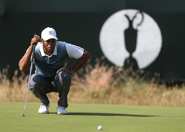 Tiger Woods of the US lines up a putt on the 3rd green during the first day of the British Open Golf championship at the Royal Liverpool golf club, Hoylake, England, Thursday July 17, 2014. (AP Photo/Peter Morrison)