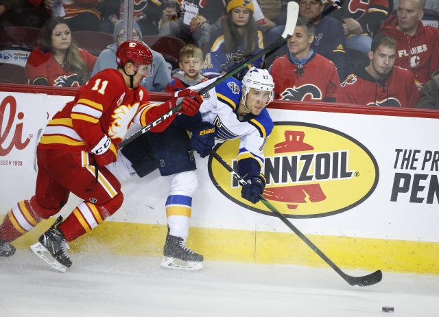St. Louis Blues' Jaden Schwartz, right, gets the puck away before being checked by Calgary Flames' Mikael Backlund during the second period of an NHL hockey game in Calgary, Saturday, Nov. 9, 2019. (Jeff McIntosh/The Canadian Press via AP)