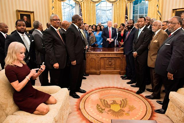 <p>FEB. 27, 2017 – Counselor to the President Kellyanne Conway (L) checks her phone after taking a photo as US President Donald Trump and leaders of historically black universities and colleges pose for a group photo in the Oval Office of the White House before a meeting with Vice President Mike Pence in Washington, DC. (Photo: Brendan Smialowski/AFP/Getty Images) </p>