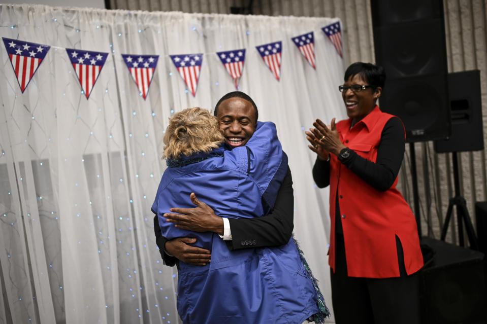 """Brooklyn Center Mayor Mike Elliott embraces Sue Low, of Maple Grove, after Elliot's inauguration ceremony, Wednesday, Jan. 2, 2019 at the Brooklyn Center Community Center, in Brooklyn Center, Minn. """"He's just an amazing guy and we're really excited for Brooklyn Center,"""" said Low, who's known Elliott since he was in high school and has worked alongside him on various committees over the years. Elliott, who emigrated from Liberia as a child, is finding just how difficult it is to turn the page on the nation's racial history as he handles the fallout from a police shooting. (Aaron Lavinsky/Star Tribune via AP)"""