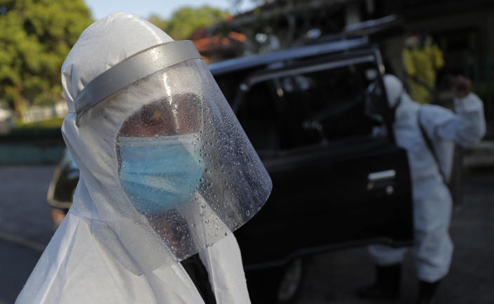 A Sri Lankan funeral service worker in protective suit stands after the cremation of a COVID-19 victim at a cemetery in Colombo, Sri Lanka, Friday, Jan. 22, 2021. Sri Lanka on Friday approved the Oxford-AstraZeneca vaccine for COVID-19 amid warnings from doctors that front-line health workers should be quickly inoculated to stop the system from collapsing. (AP Photo/Eranga Jayawardena)