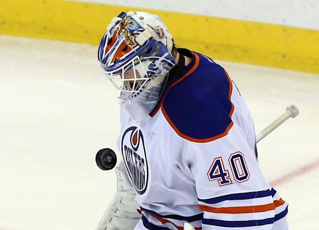 Edmonton Oliers goaltender Devan Dubnyk (40) makes a chest save against the Ottawa Senators during the second period of an NHL hockey in Ottawa, Saturday, Oct. 19, 2013. (AP Photo/The Canadian Press, Fred Chartrand)