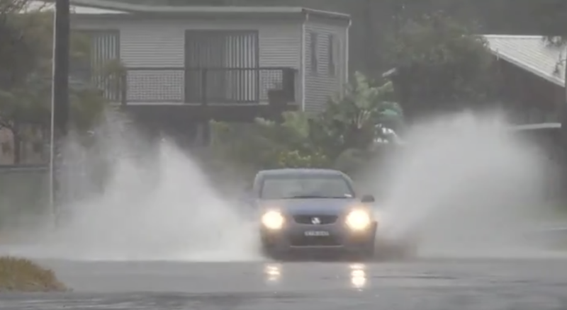 Evacuation orders are now in place in several areas in NSW. A car drives through flood waters.