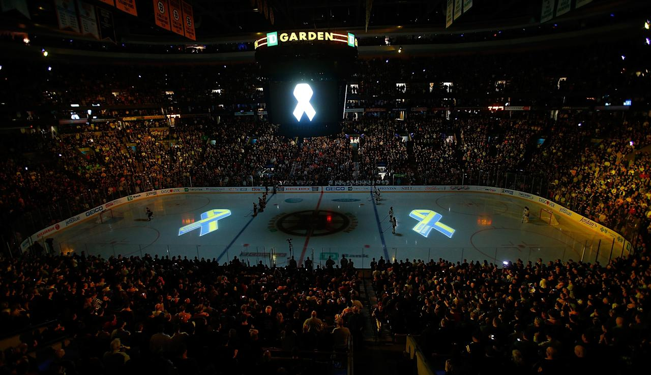 BOSTON, MA - APRIL 17:  Images of the Boston Marathon Memorial Ribbon are projected on the ice during pre-game ceremonies in remembrance of the Boston Marathon bombing victims before a game between the Buffalo Sabres and the Boston Bruins at TD Garden on April 17, 2013 in Boston, Massachusetts.  (Photo by Jim Rogash/Getty Images)