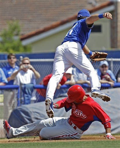 Toronto Blue Jays third baseman Omar Vizquel leaps over the sliding Shane Victorino on a wide throw after Victorino had a first-inning triple during the Blue Jays spring training baseball game against the Philadelphia Phillies in Dunedin, Fla., Sunday, March 18, 2012. (AP Photo/Kathy Willens)