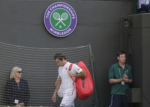Switzerland's Roger Federer leaves the court after losing his men's quarterfinals match against Kevin Anderson of South Africa, at the Wimbledon Tennis Championships, in London, Wednesday July 11, 2018. (AP Photo/Ben Curtis)