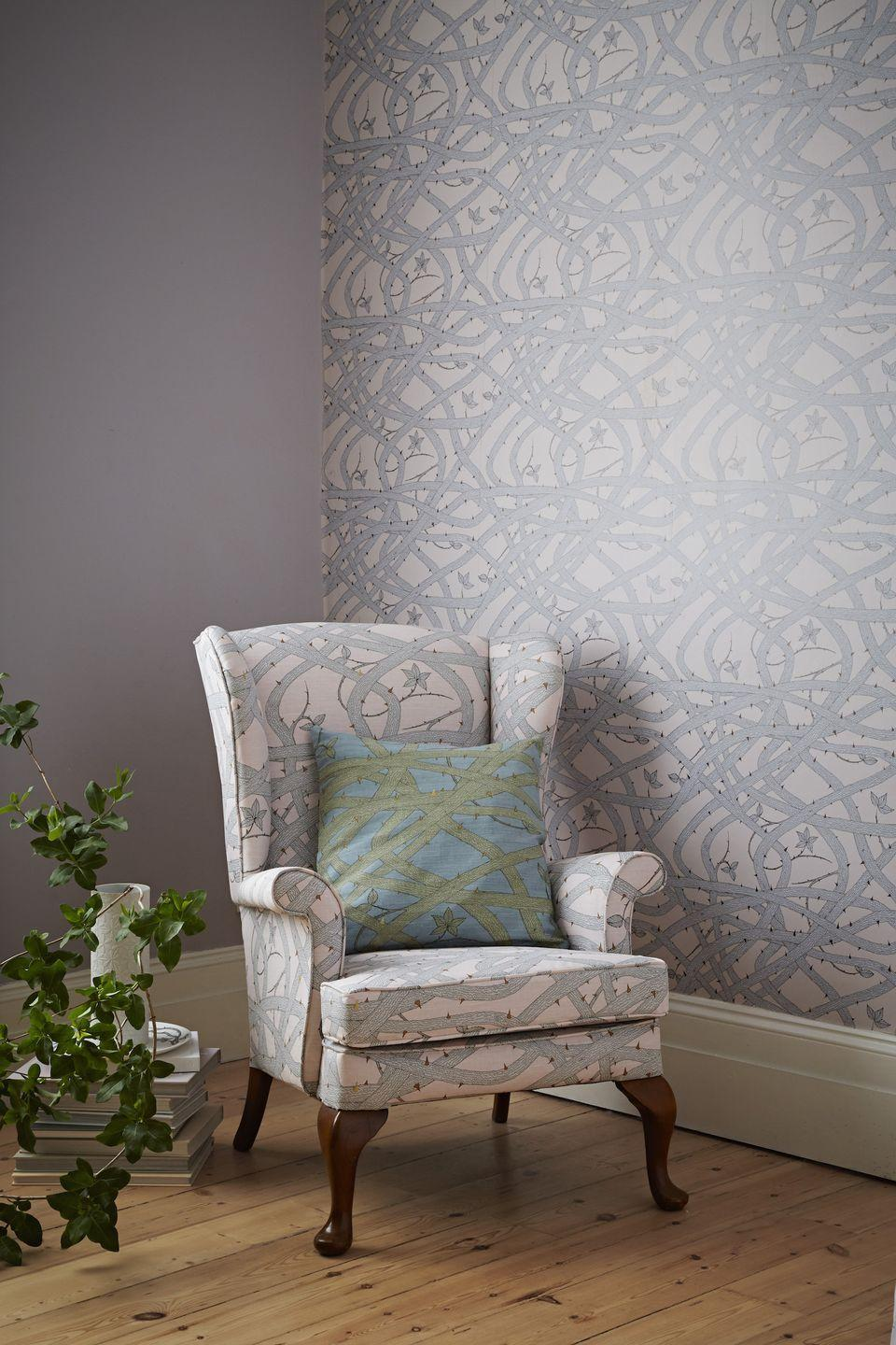 """<p>This lovely Brambleweb wallpaper is used as a feature on one wall with a complementary paint shade on the other walls. To take the scheme one stage further, why not use fabric in the same design to cover an armchair?</p><p>'Living rooms are the obvious place for wallpaper, you can make a statement or add atmosphere. Paper the entire room and ceilings to envelop the space, Brambleweb wallpaper is perfect for this, the tangled vines appear to have been growing up the walls for years, like a modern day sleeping beauty,' says <a href=""""https://www.abigailedwards.com/"""" rel=""""nofollow noopener"""" target=""""_blank"""" data-ylk=""""slk:Abigail Edwards"""" class=""""link rapid-noclick-resp"""">Abigail Edwards</a>, Wallpaper, Fabric and Accessory Designer.</p><p>Top Tip: You could even add a cushion in the same fabric but a contrasting shade for a complete look.<br></p><p>Pictured: Brambleweb wallpaper in Nude, <a href=""""https://www.abigailedwards.com/shop/brambleweb-wallpaper-nude"""" rel=""""nofollow noopener"""" target=""""_blank"""" data-ylk=""""slk:Abigail Edwards"""" class=""""link rapid-noclick-resp"""">Abigail Edwards</a></p>"""