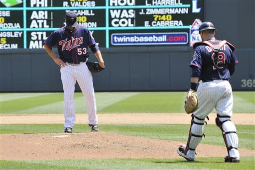 Minnesota Twins catcher Ryan Doumit, right, heads to the mound to chat with pitcher Nick Blackburn after Blackburn gave up back-to-back home runs to Chicago White Sox' Adam Dunn and Alex Rios in the fifth inning of a baseball game, Wednesday, June 27, 2012 in Minneapolis. The White Sox won 12-5. (AP Photo/Jim Mone)