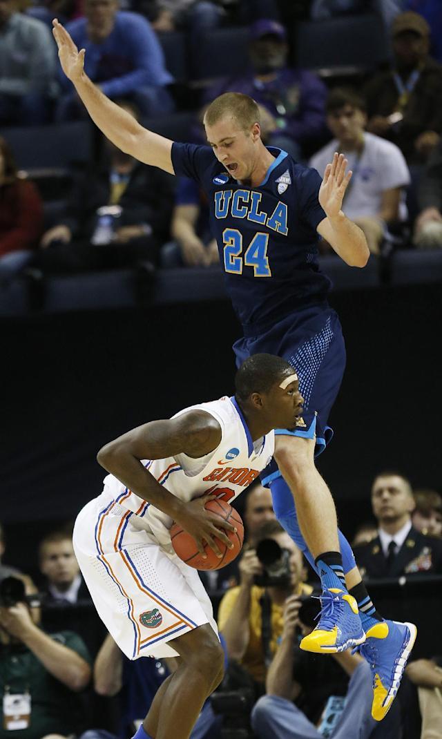 UCLA forward Travis Wear (24) defends Florida forward Dorian Finney-Smith (10) during the first half in a regional semifinal game at the NCAA college basketball tournament, Thursday, March 27, 2014, in Memphis, Tenn. (AP Photo/John Bazemore)