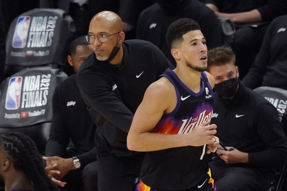Phoenix Suns guard Devin Booker, right, jogs past head coach Monty Williams after shooting a three point basket during the second half of Game 2 of basketball's NBA Finals against the Milwaukee Bucks, Thursday, July 8, 2021, in Phoenix. (AP Photo/Matt York)