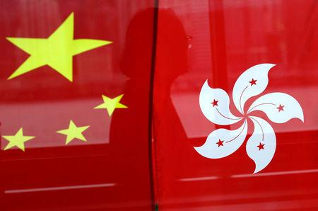 FILE PHOTO - A woman is reflected in a window behind Chinese and Hong Kong flags after celebrations commemorating the 20th anniversary of Hong Kong's handover to Chinese sovereignty from British rule, in Hong Kong