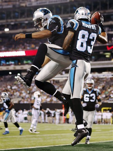 Carolina Panthers quarterback Cam Newton, left, and wide receiver Louis Murphy (83) celebrate after they connected for a touchdown during the first half of a preseason NFL football game against the New York Jets, Sunday, Aug. 26, 2012, in East Rutherford, N.J. (AP Photo/Julio Cortez)