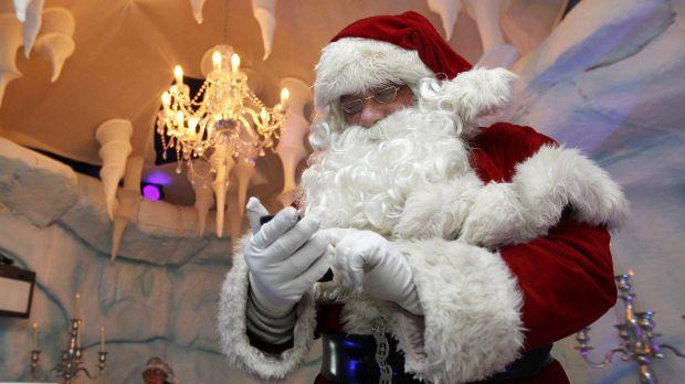 Actor David Warren, who has been playing Santa for the past ten years, checks his mobile phone during a break at Santa's Grotto in Selfridges department store in London in 2011.
