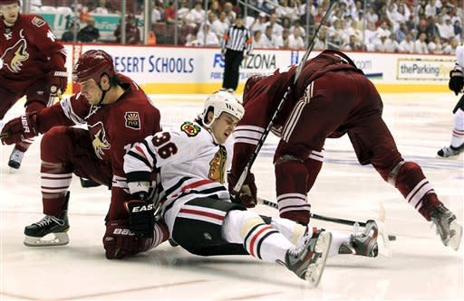 Chicago Blackhawks' Dave Bolland (36) gets upended by Phoenix Coyotes' Rostislav Klesla, left, of the Czech Republic, and Michal Rozsival, right, of the Czech Republic, during the second period in Game 1 of an NHL hockey Stanley Cup first-round playoff series, Thursday, April 12, 2012, in Glendale, Ariz. (AP Photo/Ross D. Franklin)