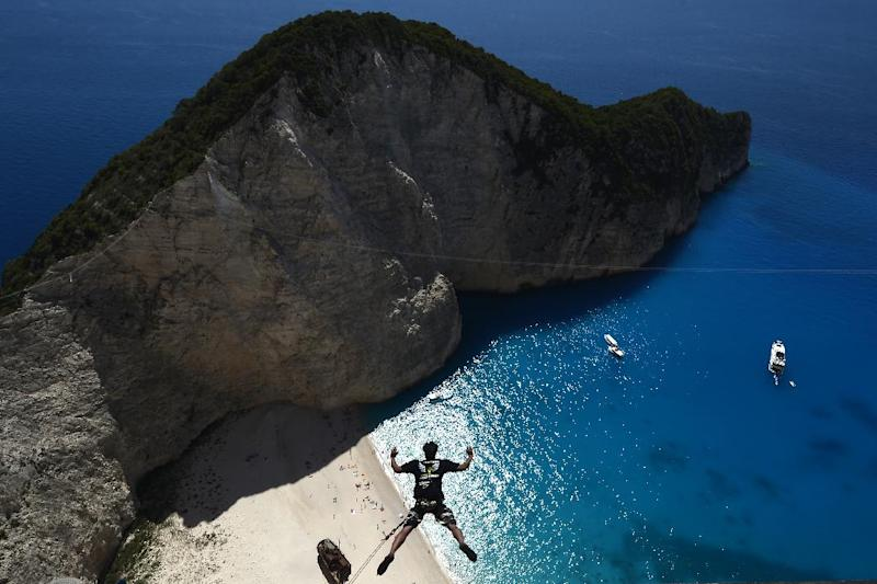 "A member of the ""Dream Jump"" team jumps from the rugged rocks overlooking Navagio beach on Zakynthos island, Greece on June 23, 2014"