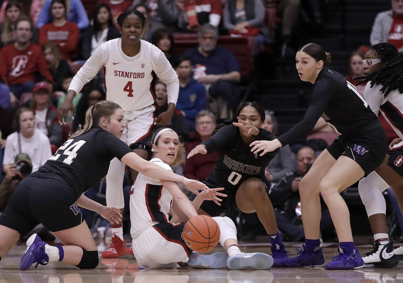 Stanford's Lexie Hull, center, passes the ball from the floor away from Washington's Ali Bamberger (24) during the first half of an NCAA college basketball game Sunday, Jan. 5, 2020, in Stanford, Calif. (AP Photo/Ben Margot)