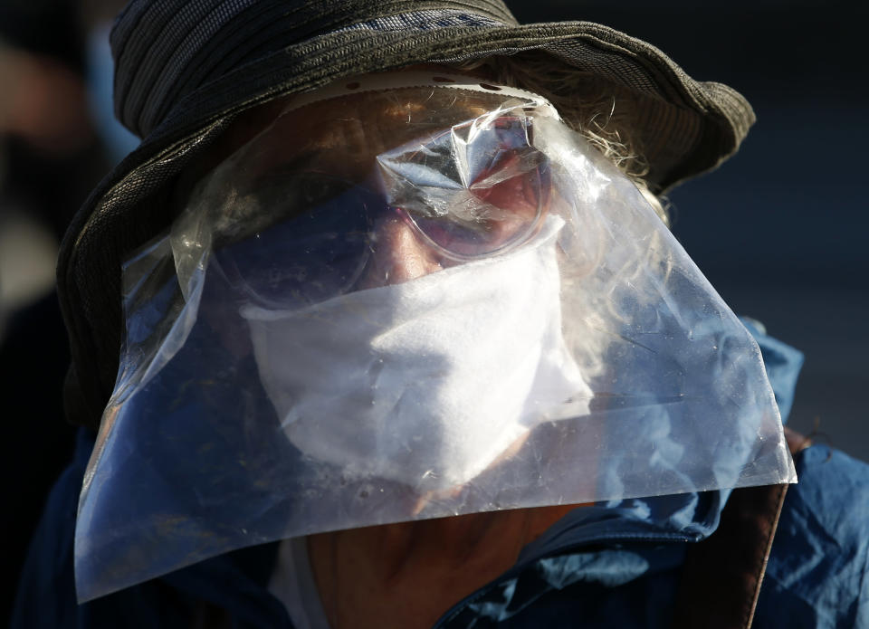 A woman wearing a homemade visor against the spread of the new coronavirus attends a protest during the curfew in front of the Serbian parliament building in Belgrade, Serbia, Thursday, April 30, 2020. Serbian opposition leaders gathered during an evening curfew to protest measures imposed by the populist authorities against the spread of the new coronavirus. Serbia's populist government in mid-March introduced some of the harshest measures in Europe, banning people over 65 years old from leaving their homes and imposing a daily and weekend curfews. (AP Photo/Darko Vojinovic)