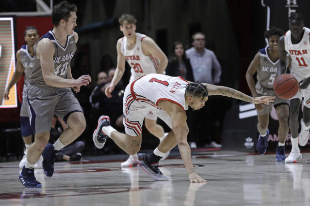 Utah forward Timmy Allen (1) reaches for the ball after being fouled by UC Davis guard Elijah Pepper (40) during the second half of an NCAA college basketball game Friday, Nov. 29, 2019, in Salt Lake City. (AP Photo/Rick Bowmer)