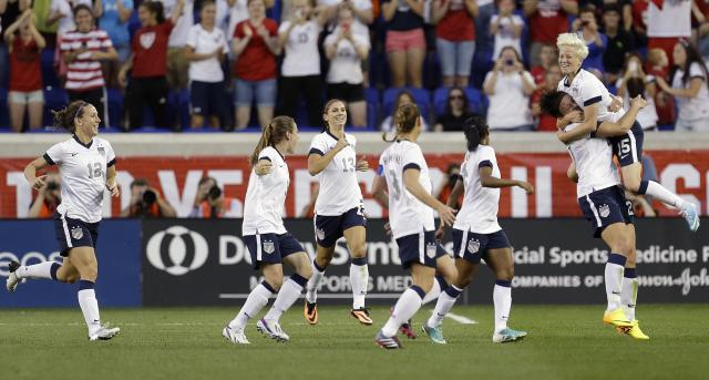 United States' Megan Rapinoe, right, celebrates with Abby Wambach as teammates rush in after Wambach scored a goal against South Korea during the first half of an international friendly soccer match at Red Bull Arena, Thursday, June 20, 2013, in Harrison, N.J. With the goal, Wambach broke Mia Hamm's national goal-scoring record. (AP Photo/Julio Cortez)