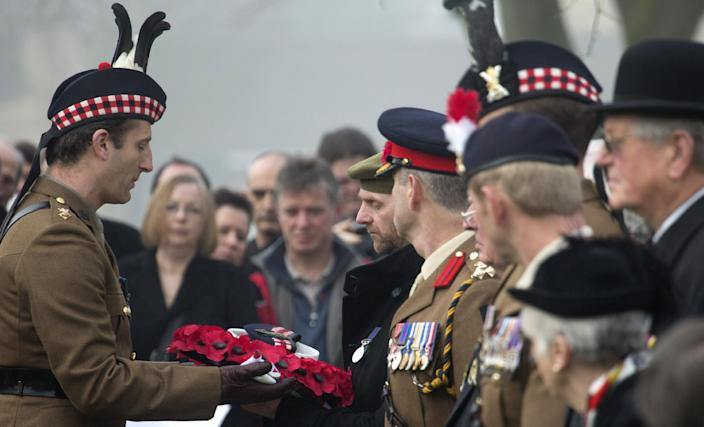 A soldier of the Scottish Division Honor Guard, left, hands over the personal effects of British World War One soldier William McAleer to his grand-nephew Stephen McLeod, center, during a reburial service at the Loos British World War One cemetery in Loos-en-Gohelle, France on Friday, March 14, 2014. Private William McAleer, of the 7th Battalion, Royal Scots Fusiliers, was killed in action on Sept. 26, 1915 during the Battle of Loos. His body was found and identified in 2010 during routine construction in the area and is being reburied with full military honors along with 19 unknown soldiers. (AP Photo/Virginia Mayo)