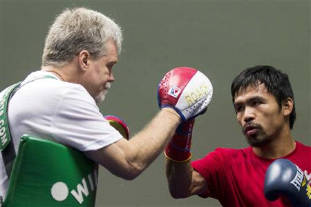Filipino boxer Manny Pacquiao practices with his coach Freddie Roach during a training session at the Venetian Macao hotel in Macau