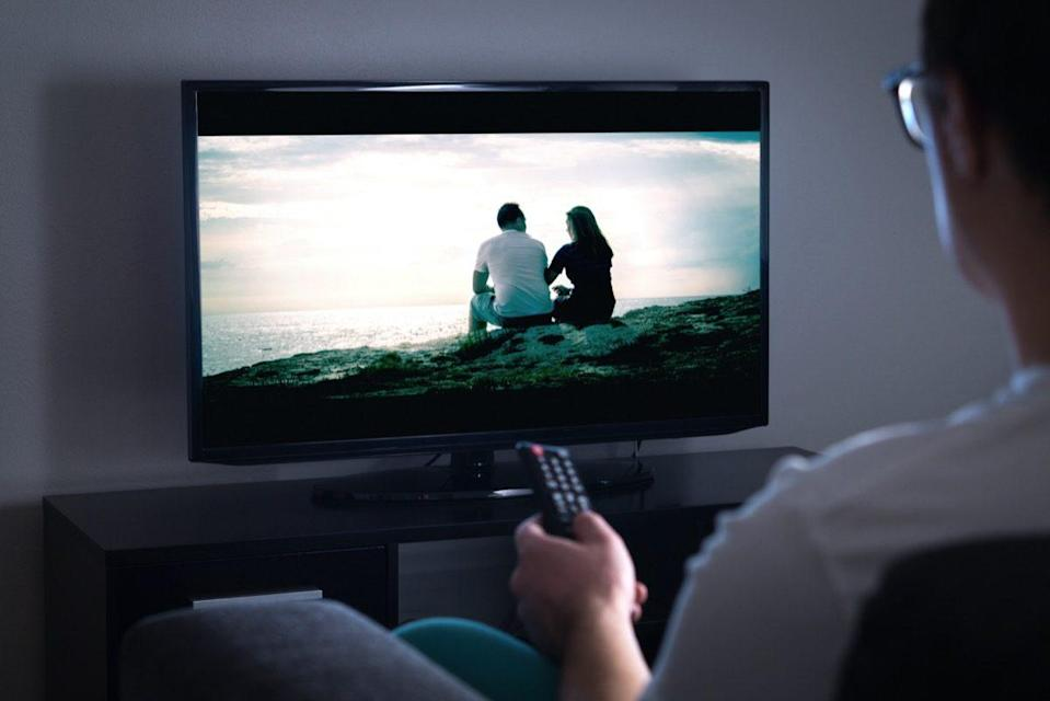 Man watching tv or streaming movie or series with smart tv at home