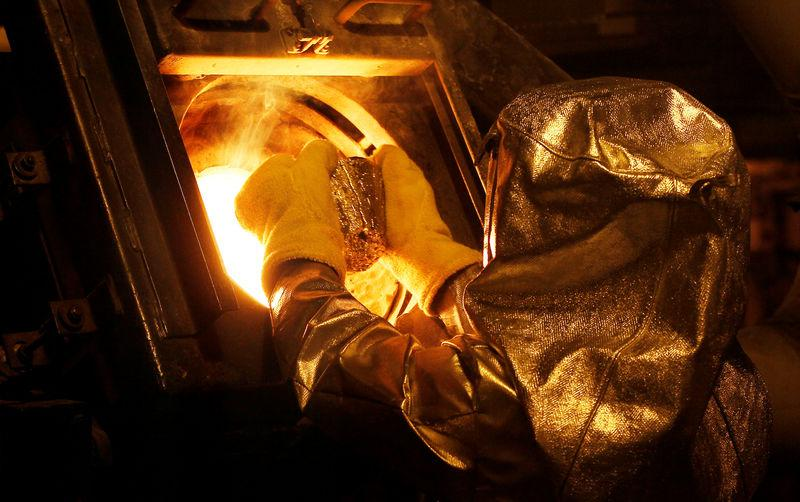 """FILE PHOTO: Senior refinery technician puts a gold """"button"""" into a furnace to be further refined to form gold dore bars at Newmont Mining's Carlin gold mine operation near Elko, Nevada"""