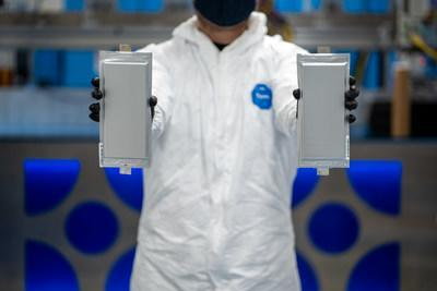 A Solid Power manufacturing engineer holds two 20 ampere hour (Ah) all solid-state battery cells for the BMW Group and Ford Motor Company. The 20 ampere hour (Ah) all solid-state battery cells were produced on Solid Power's Colorado-based pilot production line.