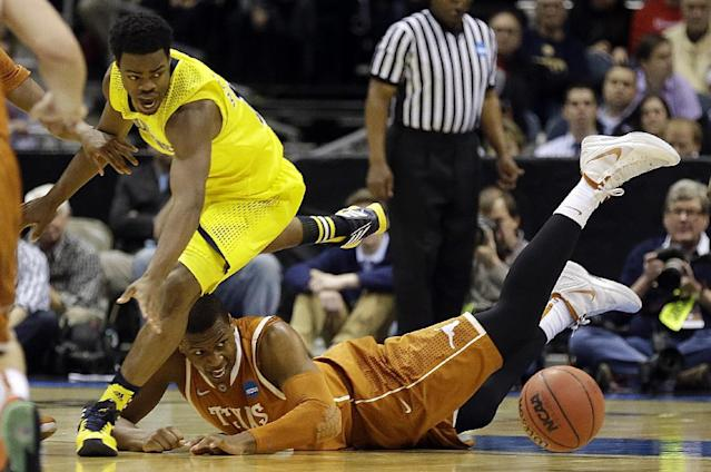 Michigan guard Derrick Walton Jr., left, and Texas forward Jonathan Holmes chase after a loose ball during the second half of a third-round game of the NCAA college basketball tournament Saturday, March 22, 2014, in Milwaukee. (AP Photo/Jeffrey Phelps)
