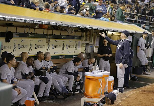 The New York Yankees wait in the dugout during a delay of the baseball game against the Oakland Athletics in the fourth inning Saturday, June 14, 2014, in Oakland, Calif. A bank of lights in left field went out causing the delay. (AP Photo/Ben Margot)