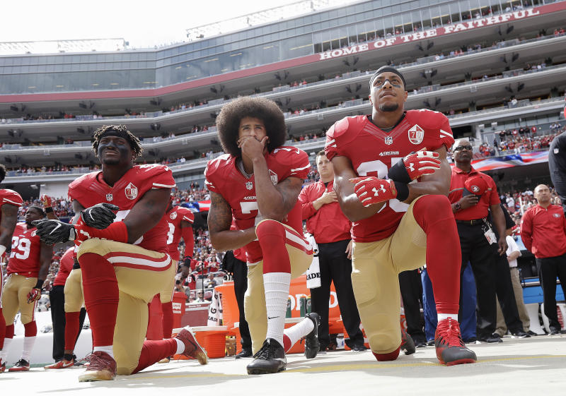 Eli Harold, Colin Kaepernick and Eric Reid kneel during the national anthem before an NFL game against the Dallas Cowboys in 2016. (AP)