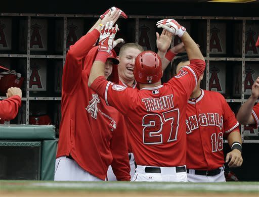 Los Angeles Angels congratulate teammate Mike Trout (27) after his home run against the Houston Astros in the third inning of an interleague baseball game in Anaheim, Calif., Sunday, April 14, 2013. (AP Photo/Reed Saxon)