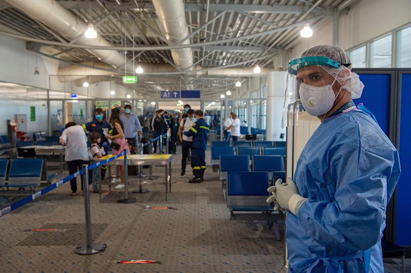 Medical staff wait to test passengers who arrive into Athens, where authorities perform random tests. (Photo: Milos Bicanski via Getty Images)