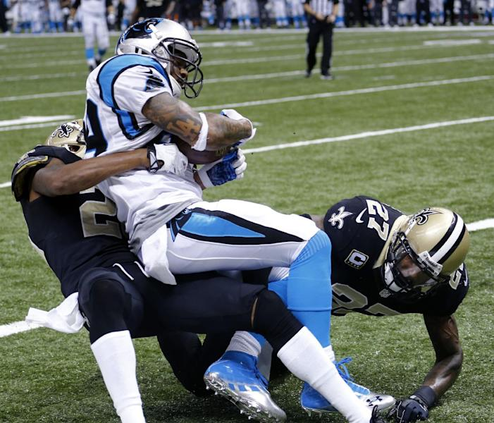 Carolina Panthers wide receiver Steve Smith (89) pulls in a touchdown pass as he is brought down by New Orleans Saints cornerback Keenan Lewis, left, and safety Malcolm Jenkins, right, in the second half of an NFL football game in New Orleans, Sunday, Dec. 8, 2013. The Saints won 31-13. (AP Photo/Bill Haber)