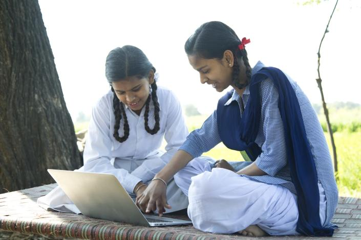 Indian school girls using laptop on field
