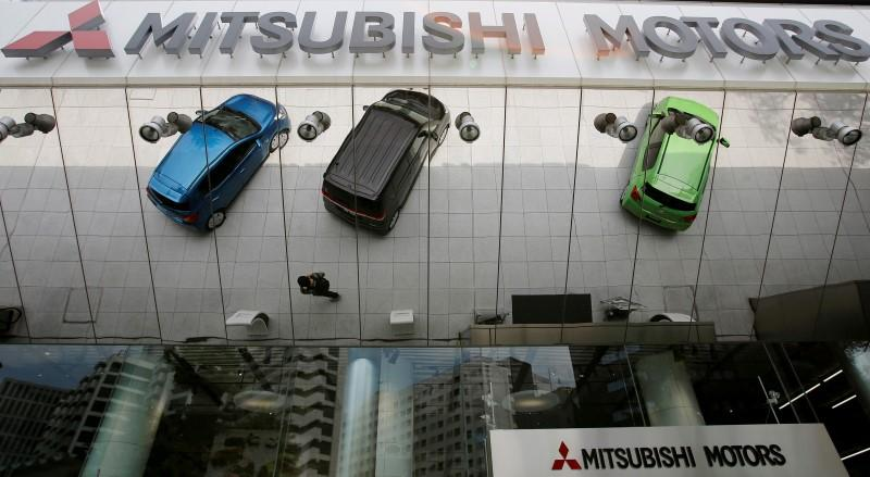 Mitsubishi Motors Corp's vehicles and a passer-by reflected on an external wall at the company headquarters in Tokyo