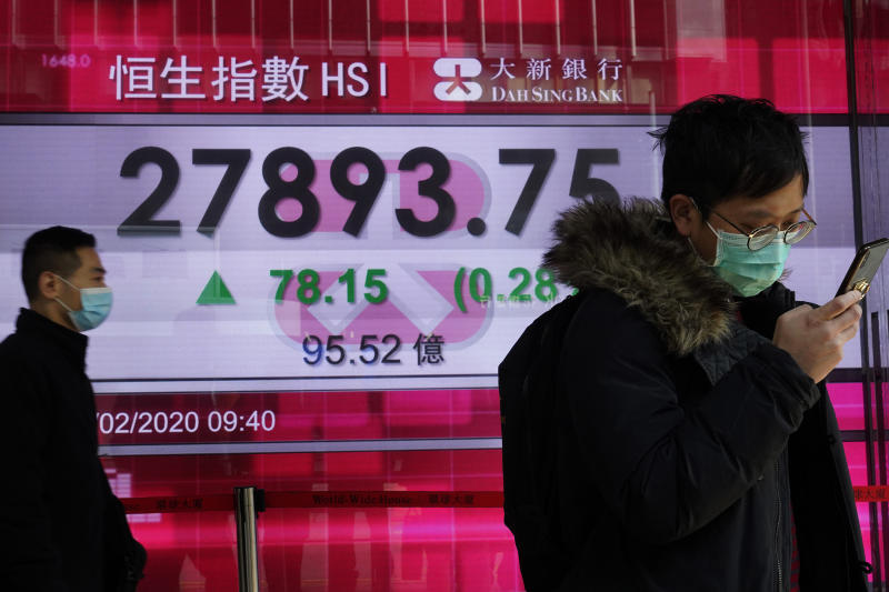 People walk past a bank electronic board showing the Hong Kong share index at Hong Kong Stock Exchange Monday, Feb. 17, 2020. Markets are mixed in Asia, with Japan's benchmark slipping 0.8% after the government reported the economy contracted in the last quarter. (AP Photo/Vincent Yu)