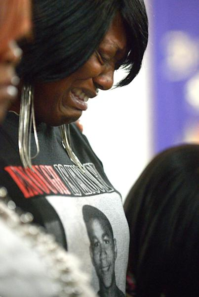 FILE - In this Sunday, July 14, 2013 file photo, Nichole Mitchell sheds tears during a sermon at the St. Paul Missionary Baptist Church in Sanford, Fla., as many in the congregation wore shirts in support of Trayvon Martin following the not guilty verdict of George Zimmerman, who had been charged in the 2012 shooting death of Martin. Nearly 70 years after Jackie Robinson was run out of town by the KKK, Sanford is absorbing what some see as another blow to race relations: Zimmerman's acquittal. (AP Photo/Phelan M. Ebenhack, File)