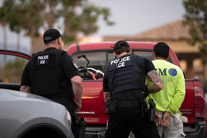 <p>A 2019 photo captures US Immigration and Customs Enforcement officers detaining a man in California.</p> (AP)