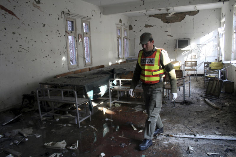 A Pakistani rescue worker strolls at a police station targeted by suicide attackers in Peshawar, Pakistan on Friday, Feb 24, 2012. Suicide bombers armed with assault rifles and grenades attacked a large police station in the northwestern Pakistan city of Peshawar early Friday, killing three officers in an assault authorities said was likely in revenge for offensives against nearby strongholds. (AP Photo/Mohammad Sajjad)
