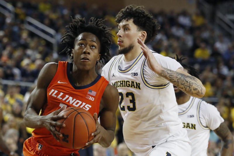 Illinois guard Ayo Dosunmu, left, is defended by Michigan forward Brandon Johns Jr., right, during the first half of an NCAA college basketball game, Saturday, Jan. 25, 2020, in Ann Arbor, Mich. (AP Photo/Carlos Osorio)